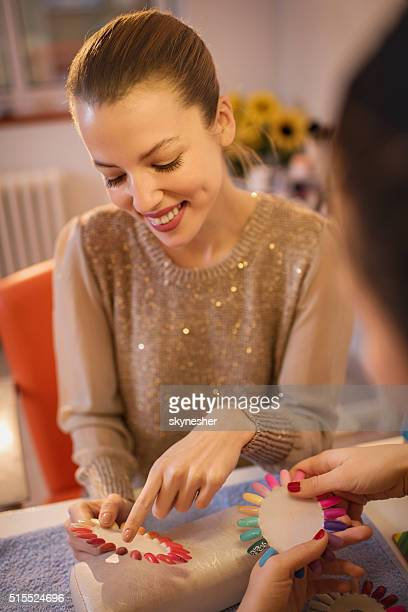 Happy woman choosing color for manicure in beauty salon.