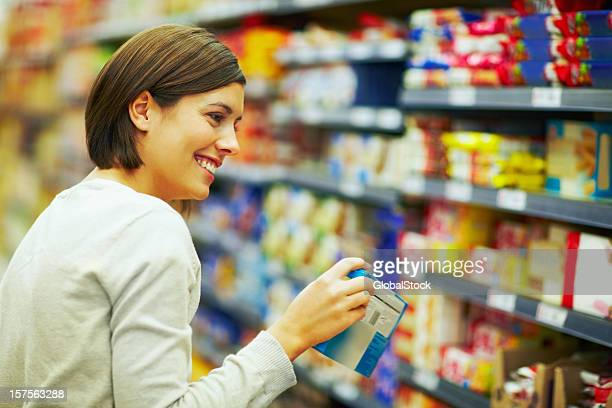 Happy woman choosing products in a supermarket