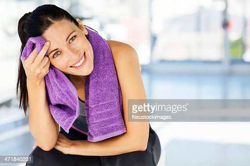 Happy Woman Cleaning Sweat From Forehead In Gym