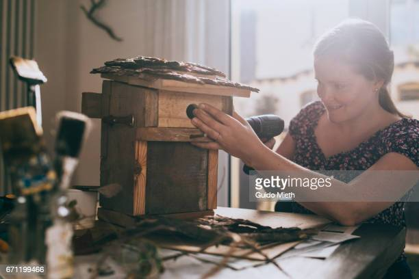 Happy woman constructing a bird house.