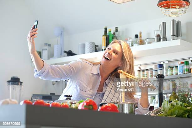 Happy woman cooking in kitchen taking a selfie