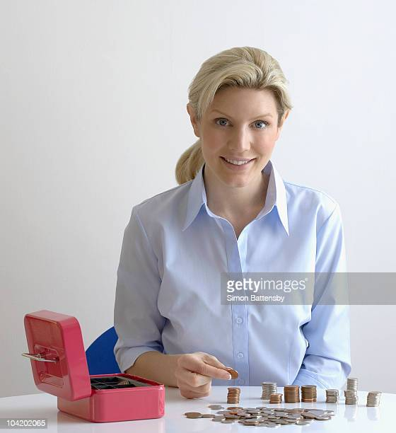 Happy woman counts coins into a cash box