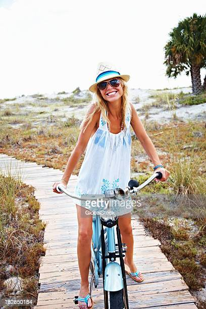 Happy woman cycling on wooden track at beach
