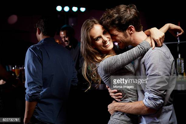 Happy woman dancing with man at nightclub