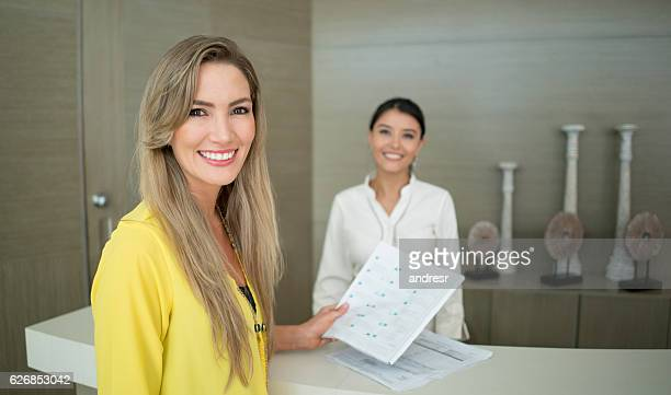 Happy woman doing the check-in at a hotel