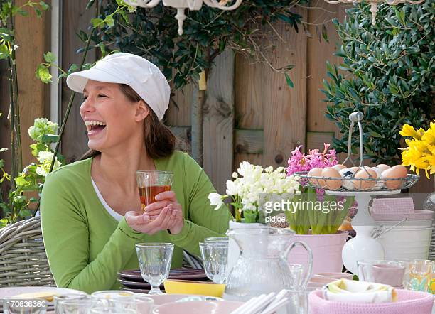happy woman drinking tea at Easter breakfast picnic table