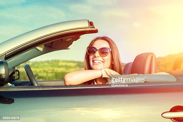 Happy woman driving a cabriolet car
