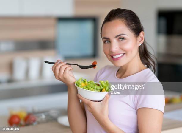 Glückliche Frau Essen einen Salat zu Hause