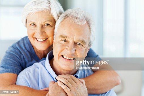 Mujer feliz acogedor hombre por detrás en su hogar