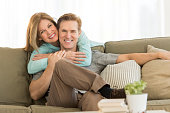 Portrait of happy couple on sofa. Woman is embracing man from behind. They are at brightly lit home.