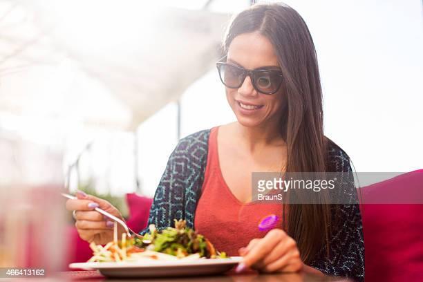 Glückliche Frau genießen einen Tag im restaurant und essen Salat.