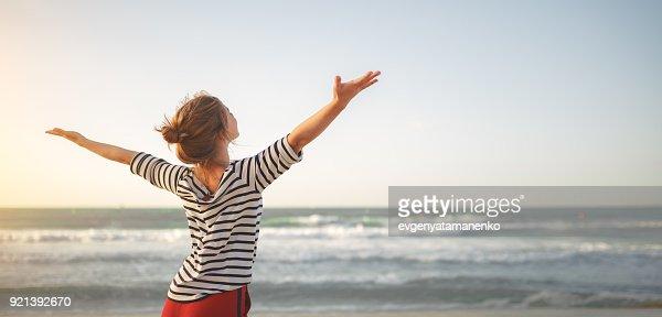 happy woman enjoying freedom with open hands on sea : Foto de stock