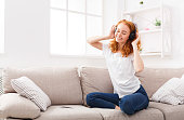 Excited girl listening to music in earphones with her eyes closed. Redhead girl wearing casual clothes, sitting on cozy beige couch with cell phone. Technology and enjoyment