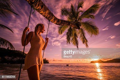 Happy woman enjoying in breathtaking sunset on the beach.
