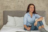 Happy mid adult woman day dreaming while relaxing on a bed with glass of wine.