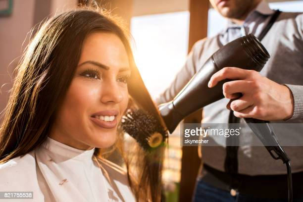 Happy woman enjoying in hair treatment at hairdresser's.