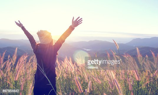 Happy Woman Enjoying Nature on meadow on top of mountain with sunrise. Outdoor. Freedom concept. : Foto stock