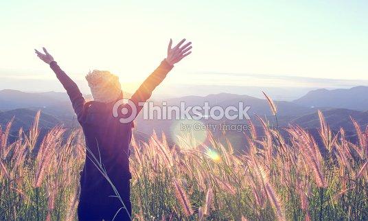 Feliz mujer disfrutando de la naturaleza en el Prado en la cima de la montaña con salida del sol. Al aire libre. Concepto de libertad. : Foto de stock