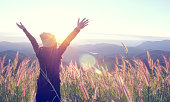 Happy Woman Enjoying Nature on grass meadow on top of mountain cliff with sunrise. Beauty Girl Outdoor. Freedom concept. Len flare effect. Sunbeams. Enjoyment.