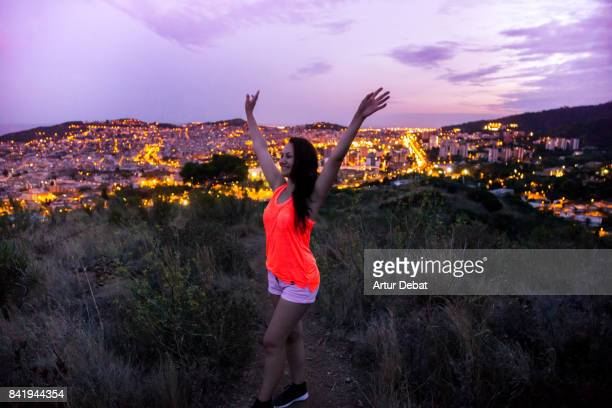 Happy woman enjoying nature walk raising arms on top of Barcelona mountains contemplating the city at dusk with elevated point of view during summer good vibes in a romantic place.