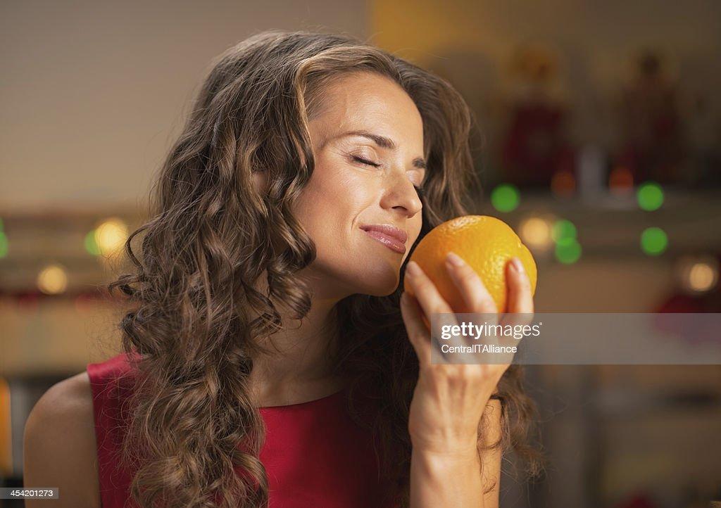 Mujer feliz disfrutando de orange en Navidad decoración cocina : Foto de stock