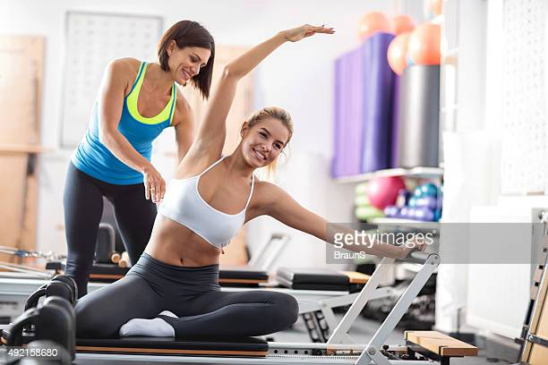 Happy woman exercising Pilates with a help of personal instructor.