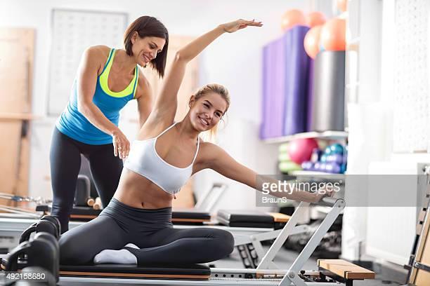 Glückliche Frau Training Pilates mit Hilfe eines persönlichen Trainer.