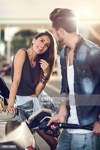 Happy woman flirting with a man at a gas station.