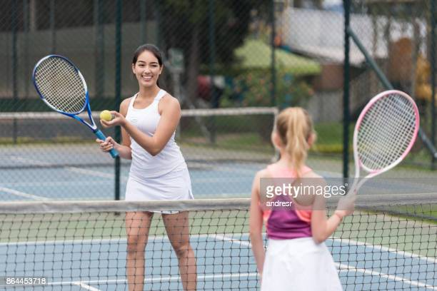 Happy woman giving tennis lessons to a little girl