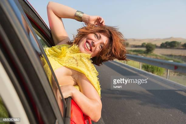 Glückliche Frau hängen von Auto Fenster