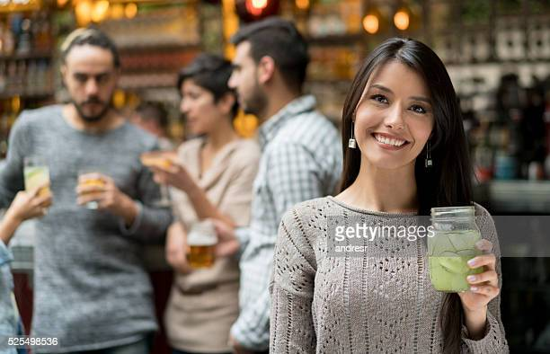 Happy woman having drinks at the bar