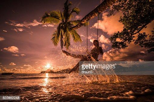 Happy woman having fun on a swing above the sea.