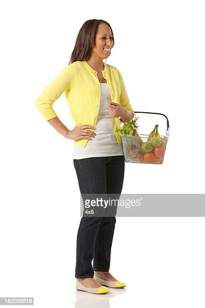 Happy woman holding a basket of fruits