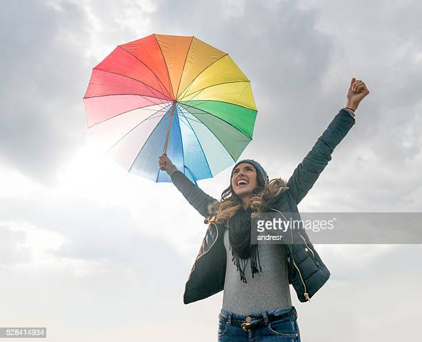 Happy woman holding a colorful umbrella