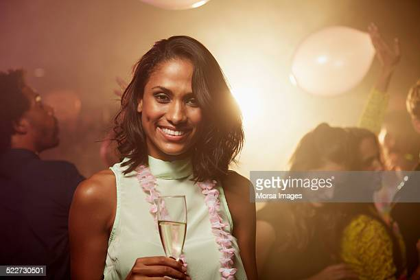 Happy woman holding champagne flute in nightclub