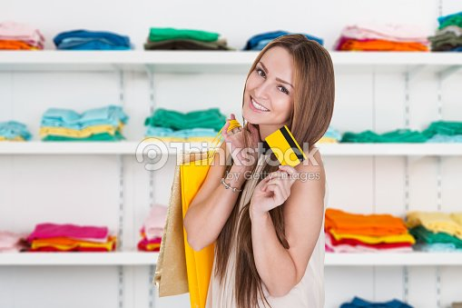 Happy Woman Holding Credit Card In Clothing Store Stock Photo