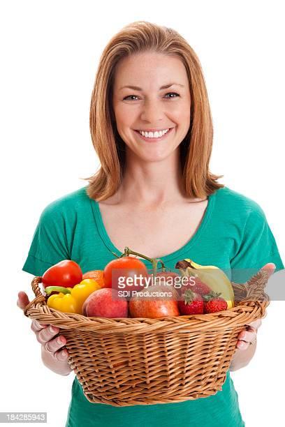 Happy Woman Holding Large Basket of Fruit