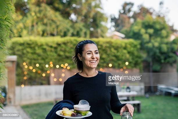 Happy woman holding plate at yard