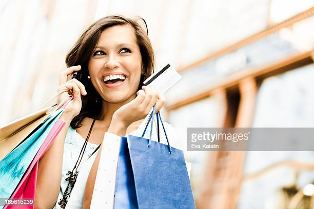 Happy woman holding shopping bags and a credit card