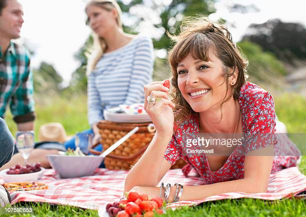 Happy woman holding strawberry with friends sitting together during picnic