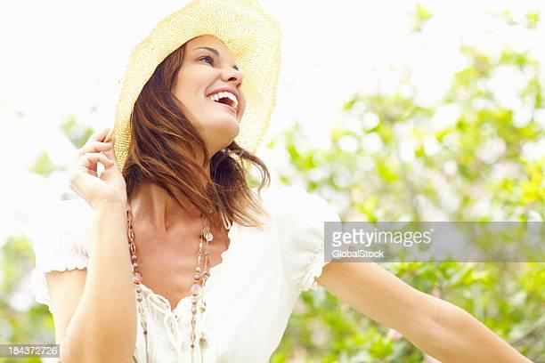 Heureuse femme tenant sunhat