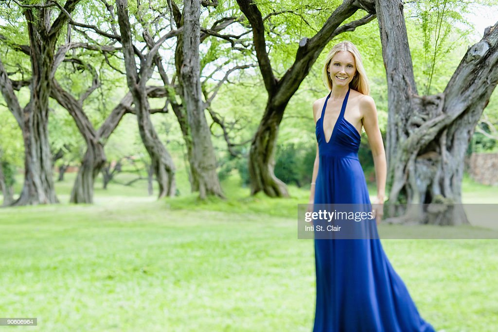 Happy woman in elegant gown in park : Stock Photo