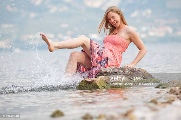 'Happy woman in Lake Garda splashing with water, Italy'
