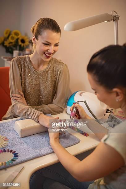 Felice donna in salone manicure di unghie godere durante il trattamento.