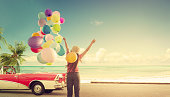Happy young woman holding colorful balloons with floating, concept of journey honeymoon in summer on tropical beach blue sky - vintage color tone