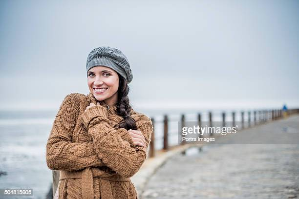 Happy woman in sweater standing at seaside