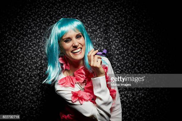 Happy woman in wig holding whistle at nightclub
