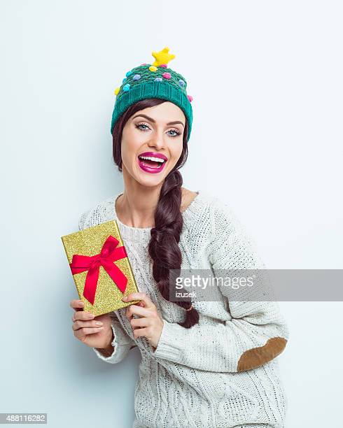 Happy woman in winter outfit holding a gift box
