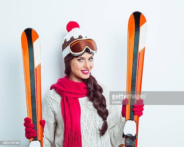 Heureuse femme en tenue d'hiver tenant ski