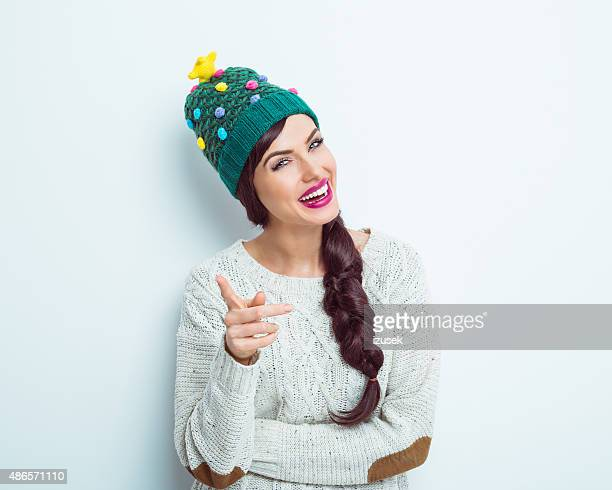 Happy woman in winter outfit pointing at camera